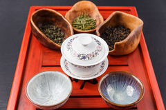 Set of teapot, three kinds of tea and four bowls Royalty Free Stock Photos