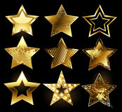 Set of textured gold stars. Set of gold stars with a variety of textures on a black background. Design with stars Royalty Free Stock Photography