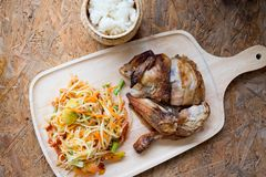 Set of Thai spicy papaya salad. Served with sticky rice and grill chicken on wood tray royalty free stock image