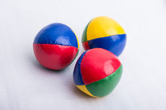 A set of three colorful juggling balls on a white surface. A set of three colorful juggling balls made from leather on a white surface Royalty Free Stock Photography