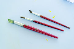 A set of three dirty paintbrushes Royalty Free Stock Photography