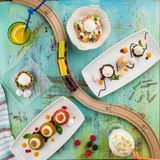 Set of three dishes Business lunch combo with kid`s railroad on blue wooden table. Top view stock image