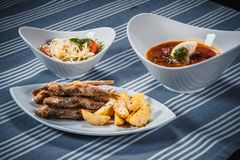 Set of three dishes. Business lunch of three dishes. Three dishes on white plates on a table with a blue tablecloth. Striped. Soup Solyanka, salad and fried Royalty Free Stock Image