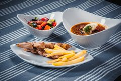 Set of three dishes. Business lunch of three dishes. Three dishes on white plates on a table with a blue tablecloth. Striped. Solyanka, vegetable salad and Stock Photography