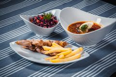 Set of three dishes. Business lunch of three dishes. Three dishes on white plates on a table with a blue tablecloth. Striped. Soup, salad and hot dish. Solyanka Stock Photo