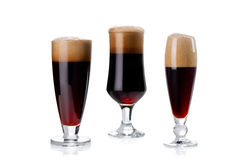 Set of three elegant glass of dark beer with foam isolated on wh Stock Photo