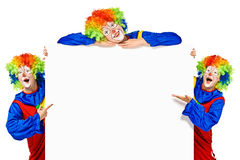 Set of three funny clown standing near board. Set of three funny clown standing over a white background and smiling Royalty Free Stock Photography