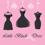 Set of  three little black dresses hang on ribbons. The composition of the three female's little black dresses hang on ribbons.Composition with chandeliers Royalty Free Stock Photography