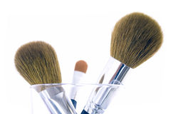 Set of three makeup brushes. For face powder, concealer and eye shadow, in a glass. Isolated on white background Stock Photography