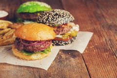Set of three mini homemade Burger with marble beef and vegetables on a old wooden background. the concept of junk food and fast fo. Od. with copy space Royalty Free Stock Image