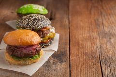 Set of three mini homemade Burger with marble beef and vegetables on a old wooden background. the concept of junk food and fast fo. Od. with copy space Royalty Free Stock Photography
