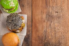Set of three mini homemade Burger with marble beef and vegetables on a old wooden background. the concept of junk food and fast fo. Od. Top View with copy space Royalty Free Stock Photos