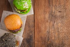 Set of three mini homemade Burger with marble beef and vegetables on a old wooden background. the concept of junk food and fast fo. Od. Top View with copy space Royalty Free Stock Photo