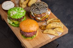 Set of three mini homemade Burger with marble beef and vegetables on a wooden Board. the concept of junk food and fast food on dar. K concrete background. Top Stock Images
