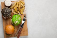 Set of three mini homemade Burger with marble beef and vegetables on a wooden Board. the concept of junk food and fast food on lig. Ht concrete background. Top Stock Photography