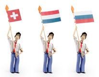 Set of paper men holding european flag. Set of three paper men lifting flags. Switzerland flag, netherland flag, rusia flag Royalty Free Stock Image