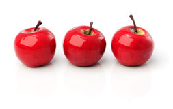 A set of three red plastic apples in a row Royalty Free Stock Image