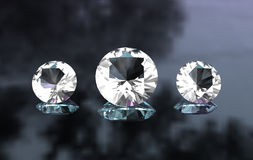 Set of three round diamonds on glossy surface Stock Photo
