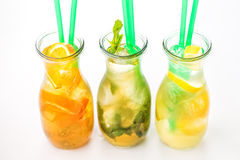 Set of three summer lemonade with ice and fruit like lemon, orange, lime and mint leaf, summer drink with soda isolated on white b Stock Photo