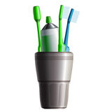 Set of three toothbrushes, toothpaste and cup Stock Image