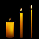 Set of three vector candles on dark background Stock Photos
