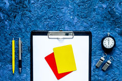 Set to judge competition. Yellow and red cards, stopwatch, whistle, pad on blue table background top view copyspace Stock Image