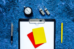 Set to judge competition. Yellow and red cards, stopwatch, whistle, pad, pen on blue table background top view Royalty Free Stock Photography