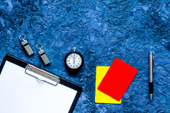 Set to judge competition. Yellow and red cards, stopwatch, whistle, pad, pen on blue table background top view copyspace Royalty Free Stock Images