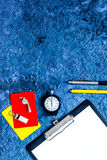 Set to judge competition. Yellow and red cards, stopwatch, whistle, pad, pen on blue table background top view copyspace Royalty Free Stock Photo
