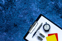 Set to judge competition. Yellow and red cards, stopwatch, whistle, pad, pen on blue table background top view copyspace. Set to judge competition. Yellow and Royalty Free Stock Image