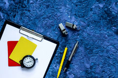 Set to judge competition. Yellow and red cards, stopwatch, whistle, pad, pen on blue table background top view copyspace Royalty Free Stock Photography
