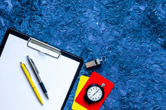 Set to judge competition. Yellow and red cards, stopwatch, whistle, pad, pen on blue table background top view copyspace Royalty Free Stock Image