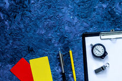 Set to judge competition. Yellow and red cards, stopwatch, whistle, pad, pen on blue table background top view copyspace Stock Image