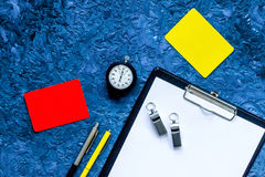 Set to judge competition. Yellow and red cards, stopwatch, whistle, pad, pen on blue table background top view copyspace Stock Photo