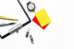 Set to judge competition. Yellow and red cards, stopwatch, whistle, pad on white background top view copyspace Stock Images