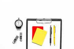 Set to judge competition. Yellow and red cards, stopwatch, whistle, pad on white background top view copyspace Stock Image