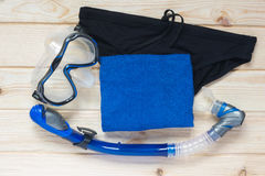 Set to swim in a sea of blue. Towel swimming trunks for the beach and a mask on the table Royalty Free Stock Photography
