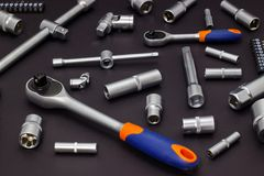 A set of tool heads for loosening screws, bolts and nuts. Ratchet screwdriver. Dark background royalty free stock image