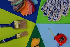Set of tools for building and treatment on colorful background: measuring tape, brushes, gloves. Modern avant-garde style.  royalty free stock images