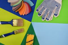 Set of tools for building and treatment on colorful background: measuring tape, brushes, gloves. Modern avant-garde style.  royalty free stock photography