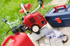 Set of tools for the care of green lawn, red chainsaw, fuel cans, a tool for adjustment. A set of tools for the care of green lawn, red chainsaw, fuel cans, a stock image