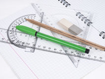 Set of tools for drawing. Protractor, pen, pencil, rules and workbook page Royalty Free Stock Photo