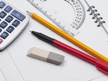 Set of tools for drawing on the workbook page. Protractor, pen, pencil, rules, calculator and workbook page Royalty Free Stock Photo
