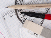 Set of tools for drawing on the workbook page. Protractor, pen, pencil, rules and workbook page Stock Photos