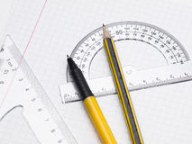 Set of tools for drawing on the workbook page. Protractor, pen, pencil, rules and workbook page Stock Photography