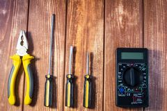 A set of tools for the electrician on a wooden background. Screwdrivers, pliers, electrical tape, tester stock photos