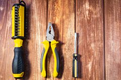 A set of tools for the electrician on a wooden background. Screwdrivers, pliers, electrical tape, tester stock photography
