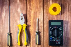A set of tools for the electrician on a wooden background. Screwdrivers, pliers, electrical tape, tester royalty free stock photo