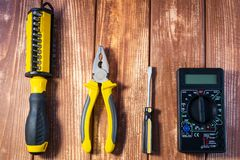 A set of tools for the electrician on a wooden background. Screwdrivers, pliers, electrical tape, tester royalty free stock photography