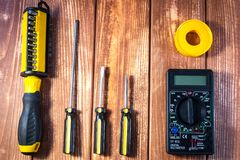 A set of tools for the electrician on a wooden background. Screwdrivers, pliers, electrical tape, tester royalty free stock images